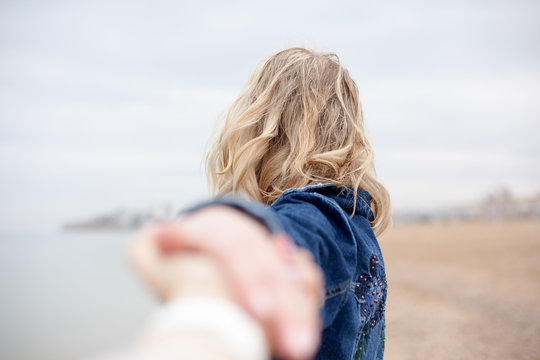 Back view of blond woman holding male hand and looking into the distance. The female walk in the shore of the sea and think about the silence of a deserted beach