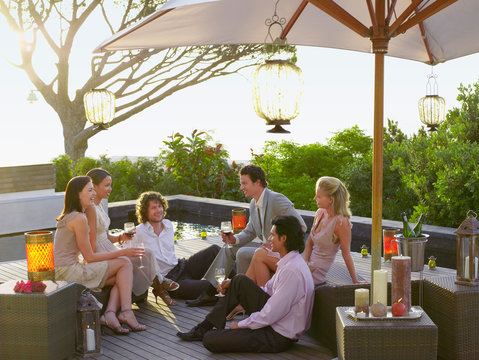 Friends enjoying a beautiful evening together drinking wine and enjoying conversation on a terrace