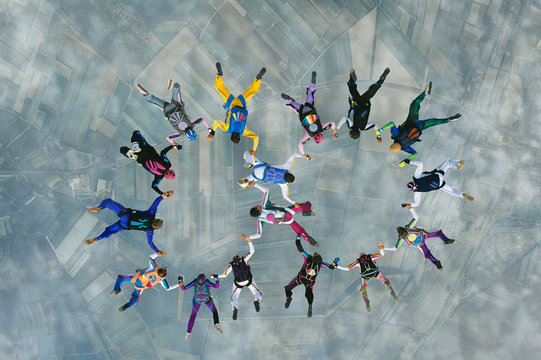 Multiple Skydivers working together and diving in a shape
