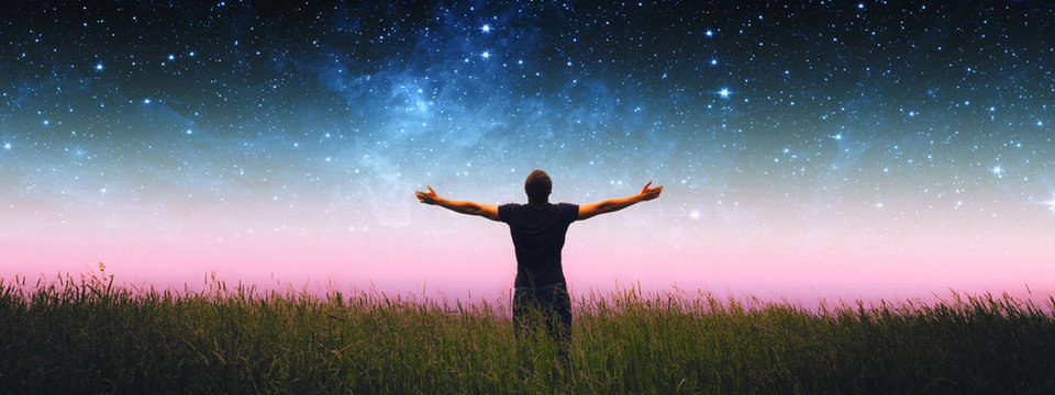 Man with arms wide open standing on the grass field against the night starry sky. Elements of this image furnished by NASA.