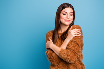 Portrait of calm cheerful girl hug herself enjoy warm fluffy sweater close eyes wear comfy clothes isolated over blue color background