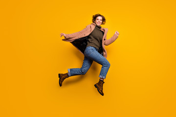 Full body profile photo of funny pretty lady jump high up rushing shopping center discounts wear casual pink coat pullover jeans leopard shoes isolated yellow color background