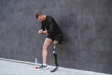 Fotomurales - Full length of handsome caucasian sportsman with artificial leg leaning on wall, looking at wristwatch and resting from running. Next to him is bottle with refreshment.