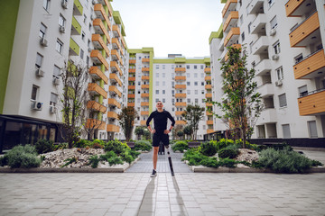 Fotomurales - Full length of handsome smiling sportsman with artificial leg standing with hands on hips outdoors surrounded by buildings. Back light.