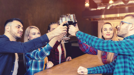 Happy millennial friends toasting and drinking red wine at pub