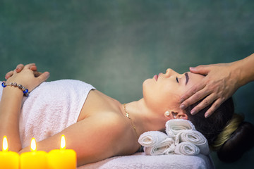 Young woman getting head massage at luxury spa