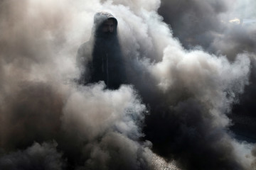 An Iraqi demonstrator walks among smoke from burning tires during ongoing anti-government protests in Kerbala
