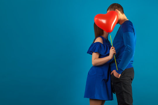 young couple in love on a blue background with red balloons. Valentine's Day