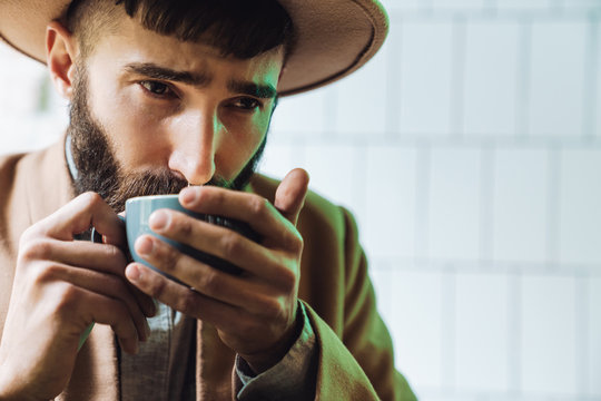 Image of attractive stylish young man wearing hat drinking tea in cafe