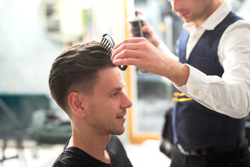 Barber is creating trendy hairstyle