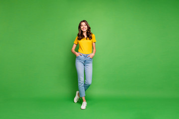 Full length body size view of her she nice attractive lovely cheerful cheery content wavy-haired girl holding hands in pockets isolated over bright vivid shine vibrant green color background Wall mural