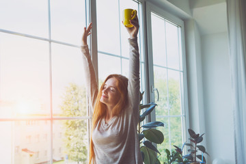 happy smiling young woman waking up, stretching, drinking coffee