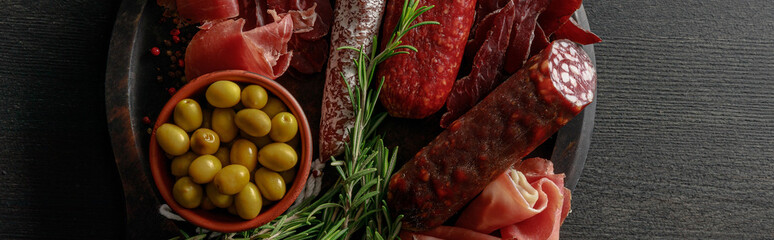 top view of delicious meat platter served with olives and herbs on wooden black table, panoramic shot