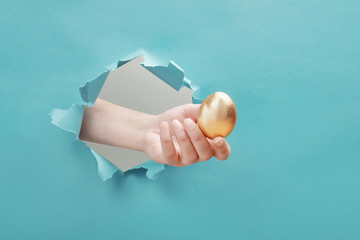 Hand gives golden egg through paper hole. Concept of profitable offer