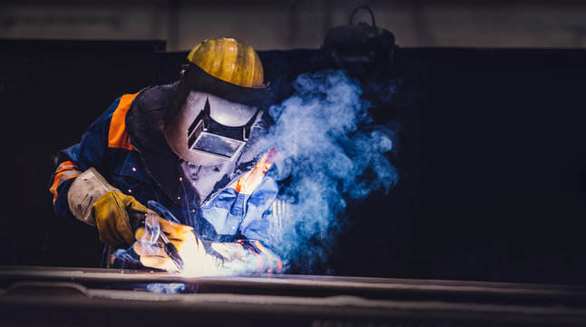 Worker welding in a factory.
