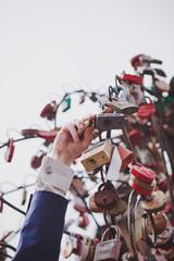 Fototapeta Wedding tradition. The groom hangs the wedding lock as a sign of eternal love. Wedding decoration element.