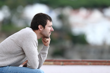 Worried man thinking looking away sitting on a bench