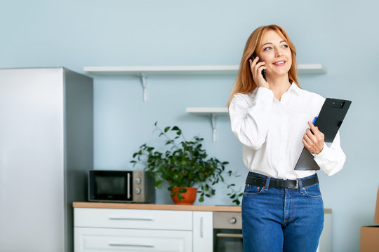Female real estate agent talking by mobile phone indoors