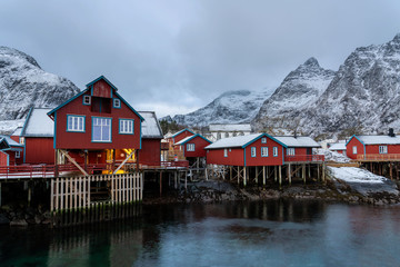 Photo sur Aluminium Pôle Lofoten village A at winter with traditional red rorbu houses and snowy mountains.