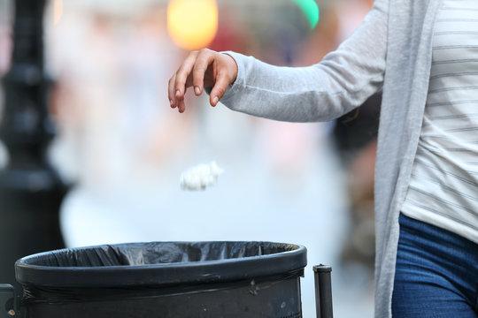 Woman hand throwing garbage to bin at evening