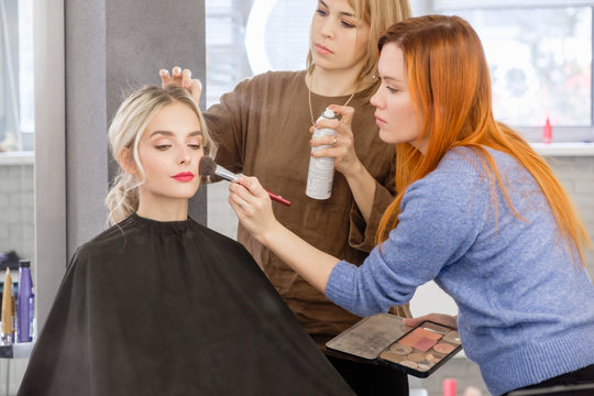 Women redhear make-up artist and hairdresser do hairstyle and stylish makeup for beautiful young blonde girl before start of fashion show. Colorful makeup design beauty and art salon concept