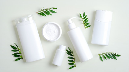 Set of SPA cosmetic containers and bottles branding mockup and green leaves. Top view shampoo bottle, lotion container, shower gel, essential oil, body cream. Bath beauty products packaging
