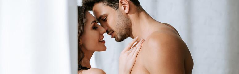 panoramic shot of shirtless man hugging happy woman