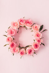 Round frame border of pink rose flower buds on pink background. Mockup blank copy space. Flat lay,...