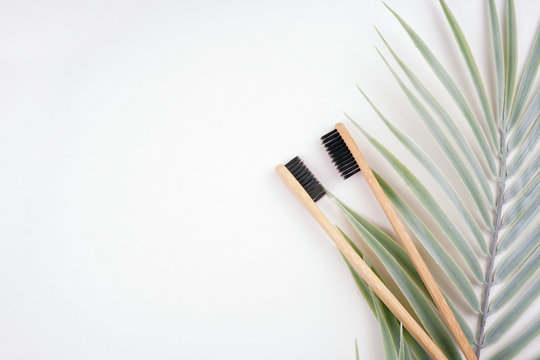 Two bamboo toothbrushes with palm leaf decoration on white background. Spa, healthcare, zero waste, treatment concept. Top view, flat lay, copy space