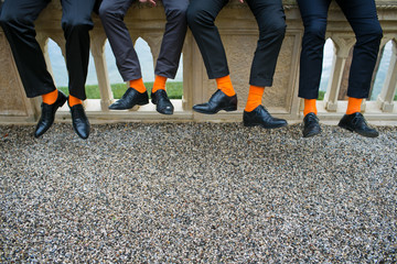 Groomsmen and the groom in tuxedos and matching orange socks, as a stylish attribute that complements the men's image and classic shoes on the wedding day before the wedding ceremony in ancient Villa