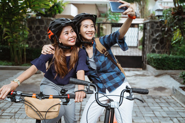 Two asian young woman wearing helmet and bags with camera cellphone make a video content on folding bike before go to campus