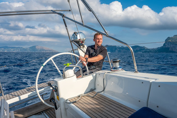 Sailor at the helm of modern sailing yacht. Mediterranean sea, near Ischia island and Capri island on the background, Italy.