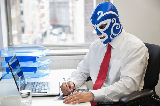 Young businessman working in office with wrestling mask on face at office desk