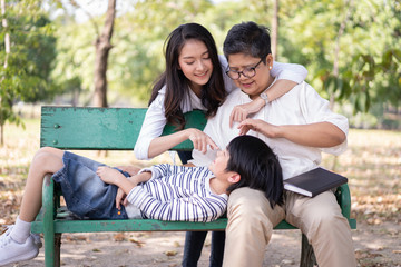 Happy Asian family and relaxing on the bench together in the public park. The concept of lifestyle in the family holiday