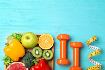 Fruits, vegetables, measuring tape and dumbbells on light blue wooden background, flat lay with space for text. Visiting nutritionist