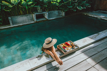 Photo sur Aluminium Bali Girl relaxing and eating fruits in the pool on luxury villa in Bali