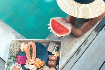 Girl relaxing and eating fruits in the pool on luxury villa in Bali