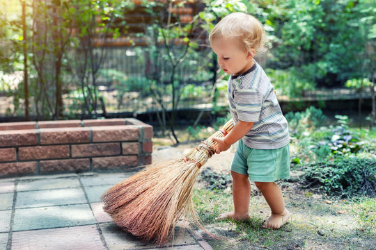 Cute adorable caucasian toddler boy playing holding broom at backyard in garden outdoors. Child little helper in t-short and shorts having fun sweeping and cleaning yard near house at countryside