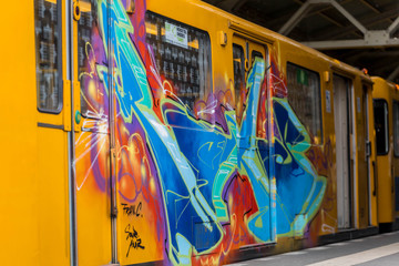 Subway train painted with graffiti is stationed in a metro station in Berlin - BERLIN / GERMANY - January  18, 2019