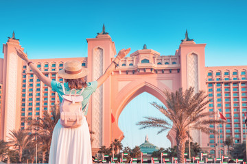 Happy asian girl traveller with backpack enjoying view of the famous luxury Atlantis hotel building on a Jumeirah Palm Island in Duba, UAE Fotomurales