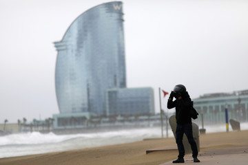 """Man uses his motorcycle helmet to protect his face from beach sand, as he takes pictures of the storm """"Gloria"""" in front of Barceloneta Beach, in Barcelona"""