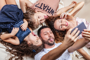 Happy family taking selfie picture with smartphone