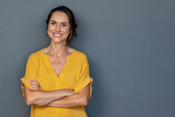 Happy mature woman smiling on grey wall Fototapete
