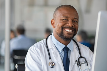 Happy smiling black doctor looking at camera