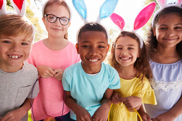 Portrait Of Five Children Wearing Bunny Ears On Easter Egg Hunt In Garden