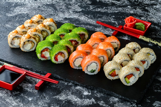 Set of sushi rolls with salmon on dark stone served with ginger and wasabi and wooden black wooden table. Fresh Japanese cuisine. Close up view on asian food. Sushi image for menu.