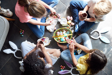 Group Of Children Sitting On Floor At Home Eating Chocolate Eggs They Have Found On Easter Egg Hunt