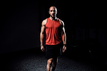 Strong muscular bodybuilder athletic man looking at camera while standing on dark studio.