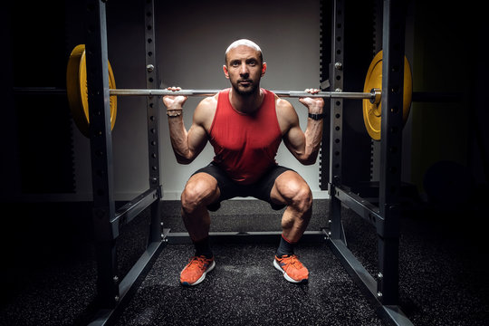 Strong muscular bodybuilder athletic man pumping up muscles with barbell on dark studio.