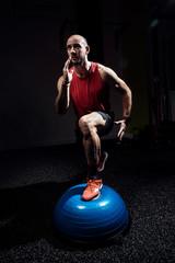 Fit athlete performing exercise on gymnastic hemisphere bosu ball on dark studio.
